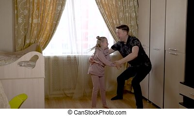 Merry dancing with a cheerful little girl in a large living room in fashionable clothes. On against a bright window.
