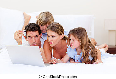 Merry family buying online lying down on bed at home