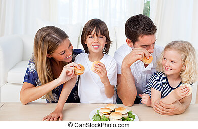 Merry family eating burgers in the kitchen at home
