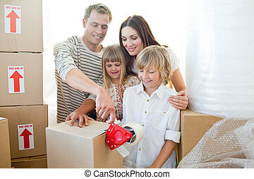Merry family packing boxes while moving house