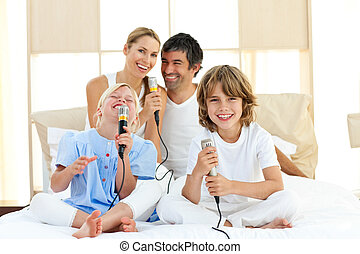 Merry family singing together through microphones