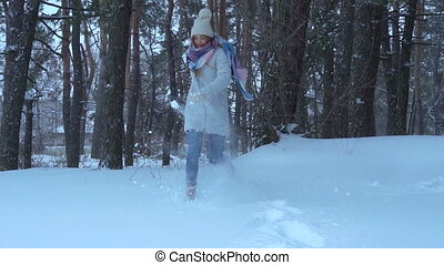 Merry girl throws the snow with their feet
