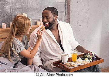 Merry international couple enjoying breakfast in the bedroom