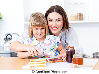 Merry little girl and her mother eating slices of bread