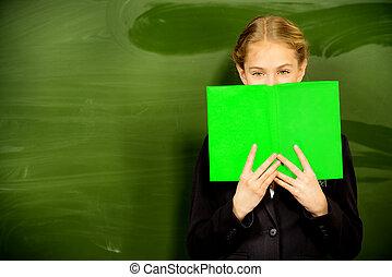 merry look - Smiling schoolgirl standing near the blackboard...