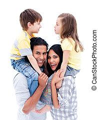 Merry parents giving their children a piggyback ride