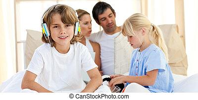 Merry siblings listening music with headphones