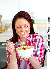 Merry woman eating a fruit salad for breakfast in the kitchen