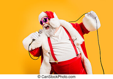 Merry x-mas carols from crazy overweight white hair christmas grandfather hold microphone sing song on noel time celebration wear style trendy suspenders hat headwear isolated yellow color background