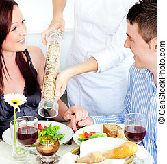 Merry young couple dining at the restaurant with waiter...