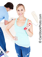 Merry young couple painting a room