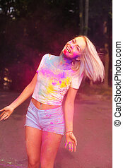 Merry young woman in white t shirt and jeans shorts posing with pink Holi powder