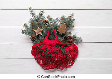 Mesh red cotton bag with Christmas fir tree branches on wooden board. Zero waste. Eco friendly Xmas.