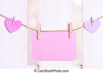 Message card and pink hearts on a string