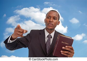 """This is an image of man holding a bible against a cloud/sky background. This image can be used to represent """"Heavenly Message"""",""""sermon"""", """"preaching"""" etc..."""