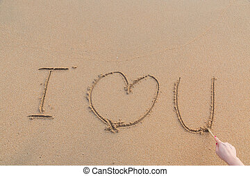 Message i love you on the sand with woman hand drawing