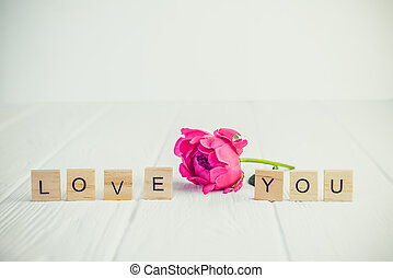 Message I love you spelled in wooden blocks with pink peony bud flower on white wooden table. Love, Valentines day background. Gift, greeting, compliment concept. Vintage tonning. Copy space.