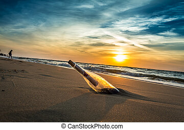 Message with letter inside the bottle on a beach in sunset