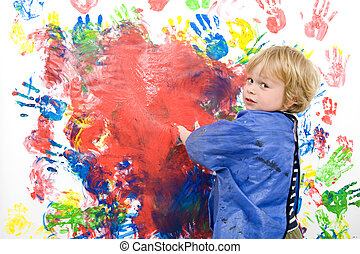 Young boy messing about with finger paint
