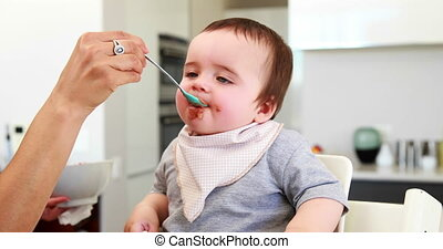 Messy baby boy being fed
