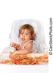 Messy baby girl eating spaghetti