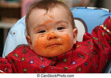 Messy Baby - a baby sitting in his high-chair with his face...