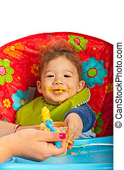 Messy baby with puree - Messy baby boy eating puree and...