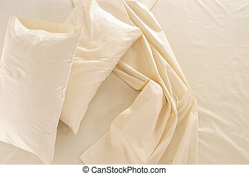 Messy bed. - Beige bed spreads.