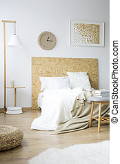 Messy bedsheets lying on a king size bed in a modern, monochromatic bedroom interior