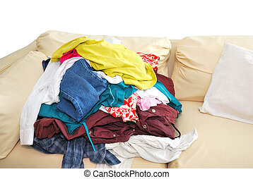 Messy and unfolded clothes on sofa isolated on white background. For lifestyle concepts.