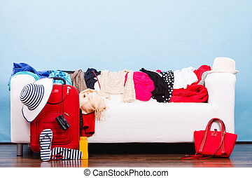 Messy colorful clothes lying on white sofa