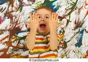 Messy kid screaming and showing his hands against painted...