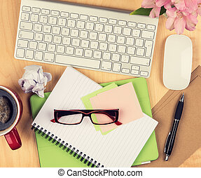 Messy office table with notepad, computer, reading glasses and coffee cup. View from above with copy space