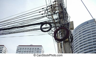 Messy wires attached to the electric pole, the chaos of cables and wires on an electric pole Thailand, concept of electricity.