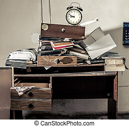 Messy workplace and alarm clock - Messy workplace with stack...