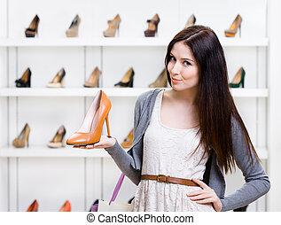 metade-comprimento, retrato, de, mulher, mantendo, sapato