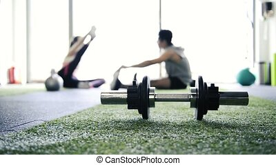 Metal barbell on the floor in gym. Couple stretching legs. -...
