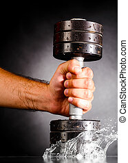 metal barbell splashes in water - male hand is splashing...