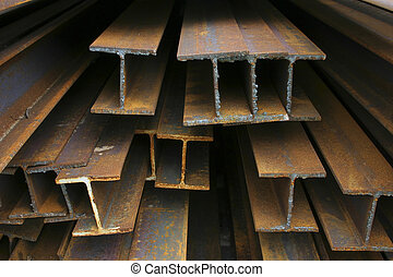 Close-up of rusty steel beams stacked at a construction site