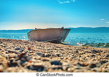 Metal boat on the shore of Lake Baikal.
