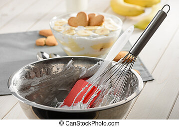Metal bowl, whisk and silicone spatula. A dessert with whipped cream