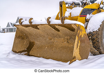 Metal bucket of a loader on snowy ground in winter