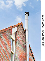 Metal chimney pipe on facade of house