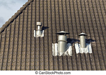 Metal chimneys - A black tiles roof with three ventilation...