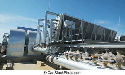 Metal chrome pipes are connected to a common water supply system for the enterprise. On the roof of an industrial building organized piping and ventilation.