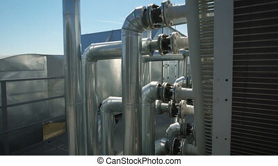 Metal chrome pipes are connected to a common water supply system for the enterprise. On the roof of an industrial building has a lot of equipment necessary for the work maintenance of the plant.