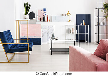 Metal coffee table with glass counter top in the middle of modern full of color living room with petrol blue armchair, powder pink sofa, shelf, maps and paintings, real photo