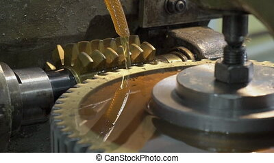 Metal cutter cuts furrows on pinion with cooling. Close-up...