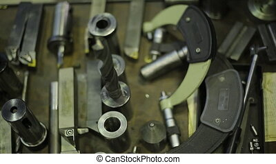 Metal cutting tools for milling and drilling machines on a wooden table in workshop, closeup.