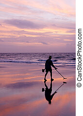 Metal Detecting at Sunrise - A man using a metal detector on...